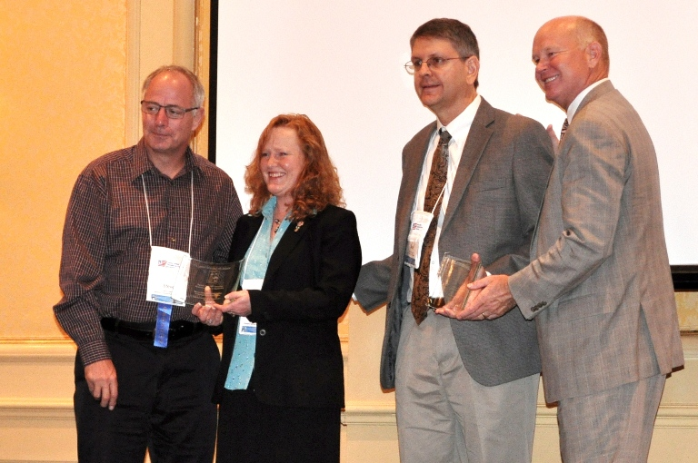 Leann Koon and Sean Campbell accept the 2012 Best of Rural ITS Award from Steve Albert (left), Rural SIG Chair, and Scott Belcher (right), ITS America President.